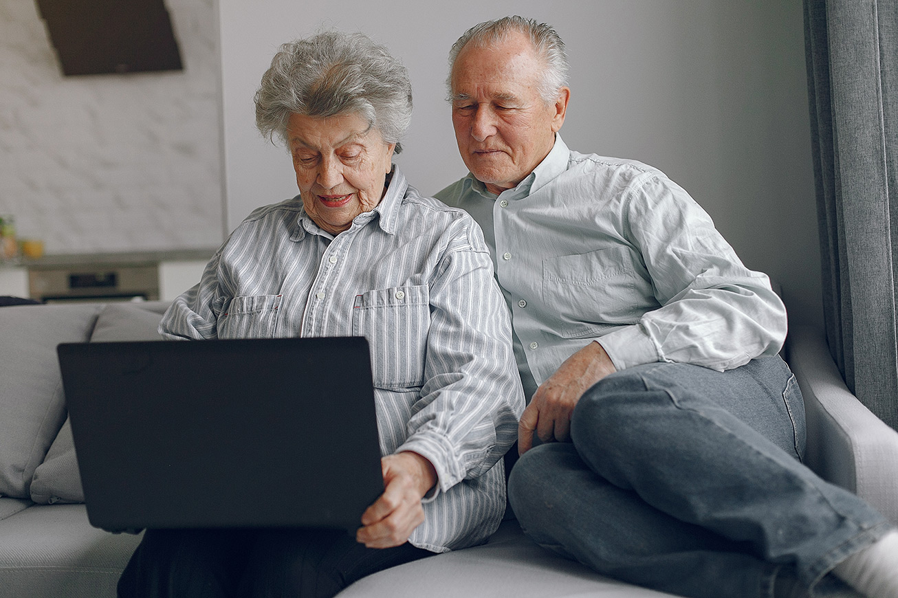 elegant-old-couple-sitting-at-home-and-using-a-laptop